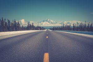 route déserte en face d'une montagne enneigée alaska