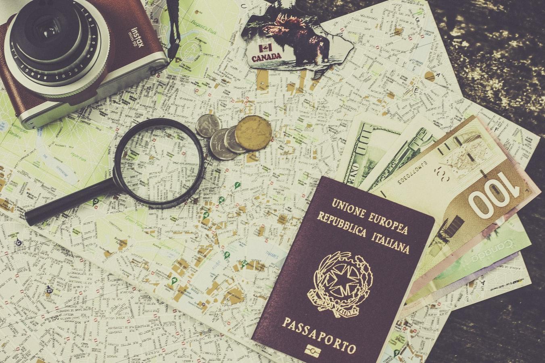 Passeport et monnaie étrangère disposés sur une carte pour organiser un voyage