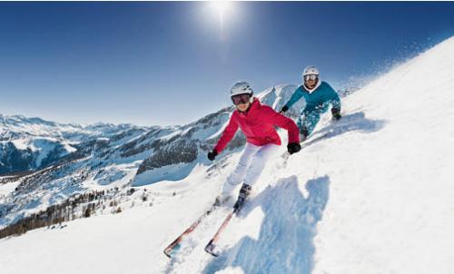 deux personnes descendant une piste à skis
